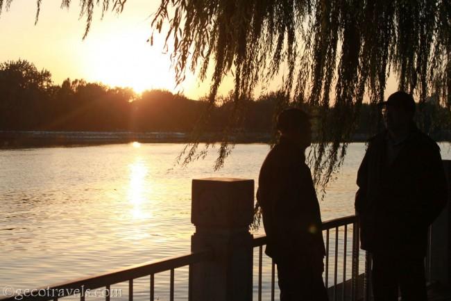 signori cinesi che parlano sul lungolago al tramonto